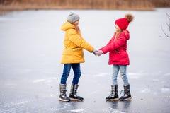 Прелестные маленькие девочки катаясь на коньках на катке стоковое фото rf