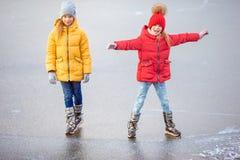 Прелестные маленькие девочки катаясь на коньках на катке стоковое изображение