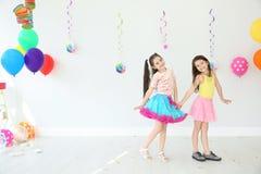 Прелестные маленькие девочки на вечеринке по случаю дня рождения внутри помещения Стоковые Изображения