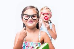 прелестные маленькие девочки с ручками и книгами партии усмехаясь на камере Стоковая Фотография RF