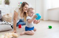 Прелестные 10 месяцев старого ребёнка играя с голубым шариком на поле на спальне Стоковое фото RF