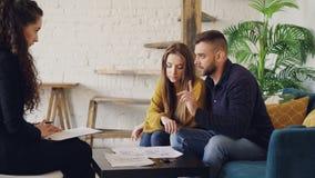 Прелестные молодые покупатели дома пар смотрят бумаги и разговаривают с риэлтором после этого усмехаясь и целуя счастливо акции видеоматериалы