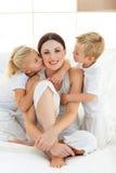 Прелестные отпрыски целуя их мать Стоковые Изображения