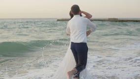 Прелестные пары новобрачных отдыхая на пляже во время захода солнца Они счастливо бегут и обнимают романтично видеоматериал