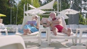 Прелестные положительные пары лежа на sunbeds около бассейна Женщина читая книгу пока человек работая с планшетом t видеоматериал