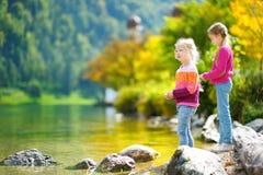 Прелестные сестры играя озером Konigssee в Германии на теплый летний день Милые дети имея уток потехи подавая и бросая ston Стоковые Изображения