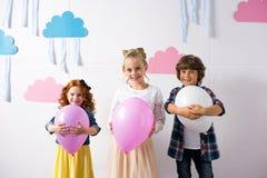 прелестные счастливые дети держа воздушные шары и усмехаясь на камере на дне рождения Стоковые Фото
