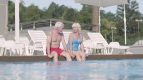 Прелестные счастливые зрелые пары сидя на краю бассейна Милый старшего обнимать человека и женщины ослабляя в гостинице сток-видео