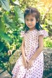 Прелестный азиатский ребенок усмехаясь и ослабляя на парке с солнечным светом, Стоковое фото RF