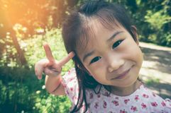 Прелестный азиатский ребенок усмехаясь и ослабляя на парке с солнечным светом, Стоковое Фото