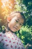 Прелестный азиатский ребенок усмехаясь и ослабляя на парке с солнечным светом, Стоковая Фотография RF