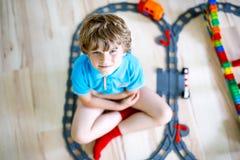 Прелестный маленький белокурый мальчик ребенк играя с красочными пластичными блоками и создавая вокзал Ребенок имея потеху с стоковые изображения