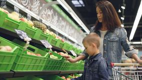 Прелестный мальчик выбирает яблока в отделе фрукта и овоща в гастрономе, его привлекательная мать акции видеоматериалы