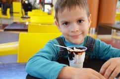 Прелестный мальчик в деловом костюме ` s бизнесмена второпях есть мороженое на ресторане во время обеда Стоковое Фото