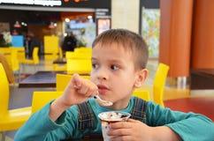 Прелестный мальчик в деловом костюме ` s бизнесмена второпях есть мороженое на ресторане во время обеда Стоковая Фотография