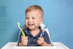 Прелестный мальчик держа 2 зубной щетки Стоковое фото RF