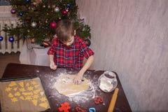 Прелестный мальчик подготавливает пряник, печет печенья в кухне рождества стоковое изображение
