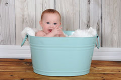 Прелестный младенец сидя в hapily зеленом washtub стоковое изображение