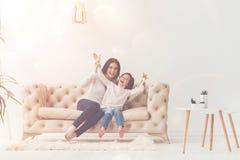 Прелестный ребенок и ее мама имея потеху на софе стоковые фото