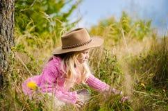Прелестный ребенок с шляпой в лесе осени усмехаясь и ослабляя стоковая фотография