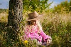 Прелестный ребенок с шляпой в лесе осени усмехаясь и ослабляя стоковое изображение