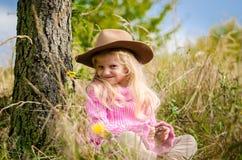 Прелестный ребенок с шляпой в лесе осени усмехаясь и ослабляя стоковые фото
