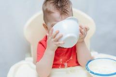 Прелестный ребёнок ест кашу себя с малой ложкой стоковые фото