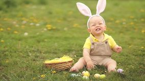Прелестный смешной ребенок с ушами зайчика играя на зеленой траве с пасхальными яйцами Ребенок смеется весело r сток-видео