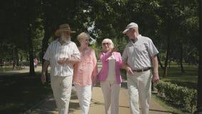 2 прелестных взрослых пары идя в парк говоря и усмехаясь Двойная дата старших пар Дружелюбная компания сток-видео