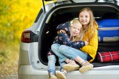 2 прелестных девушки при чемодан идя на каникулы с их родителями 2 дет смотря вперед для поездки или перемещения Autu Стоковая Фотография RF