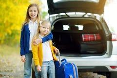 2 прелестных девушки при чемодан идя на каникулы с их родителями 2 дет смотря вперед для поездки или перемещения Autu Стоковые Фотографии RF