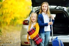 2 прелестных девушки при чемодан идя на каникулы с их родителями 2 дет смотря вперед для поездки или перемещения Autu стоковые изображения rf