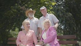 2 прелестных зрелых пары говоря и усмехаясь на стенде в парке лета Двойная дата старших пар Дружелюбный видеоматериал