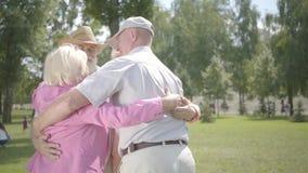 2 прелестных зрелых пары обнимая в парке совместно стоя в круге Двойная дата старших пар Дружелюбный акции видеоматериалы