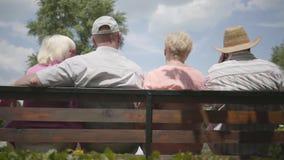 2 прелестных зрелых пары сидя на стенде и говоря совместно Outdoors зрелых людей отдыхая Жизнерадостный старший сток-видео