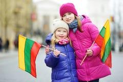 2 прелестных маленьких сестры празднуя литовский День независимости держа tricolor Lithuanian сигнализируют Стоковые Фото