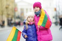 2 прелестных маленьких сестры празднуя литовский День независимости держа tricolor Lithuanian сигнализируют Стоковое фото RF