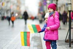 2 прелестных маленьких сестры празднуя литовский День независимости держа tricolor Lithuanian сигнализируют Стоковое Изображение RF