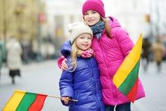 2 прелестных маленьких сестры празднуя литовский День независимости держа tricolor Lithuanian сигнализируют Стоковое Изображение