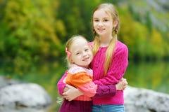 2 прелестных маленьких сестры смеясь над и обнимая на теплый и солнечный летний день около озера Konigssee, Германии Стоковая Фотография
