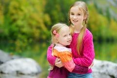 2 прелестных маленьких сестры смеясь над и обнимая на теплый и солнечный летний день около озера Konigssee, Германии Стоковое Изображение