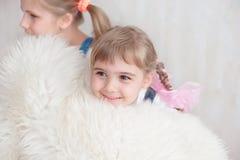 2 прелестных маленьких сестры смеясь над и обнимая одином другого Стоковые Изображения RF
