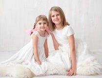 2 прелестных маленьких сестры смеясь над и обнимая одином другого Стоковая Фотография