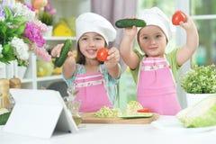 2 прелестных маленькой девочки в рисбермах имея потеху Стоковые Изображения