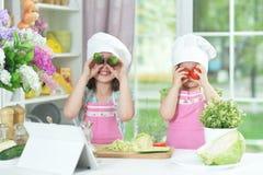 2 прелестных маленькой девочки в рисбермах имея потеху Стоковые Фотографии RF