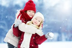 2 прелестных маленькой девочки имея потеху совместно в красивом парке зимы Красивые сестры играя в снеге Стоковая Фотография