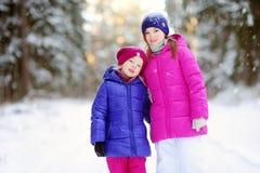 2 прелестных маленькой девочки имея потеху совместно в красивом парке зимы Красивые сестры играя в снеге Стоковая Фотография RF
