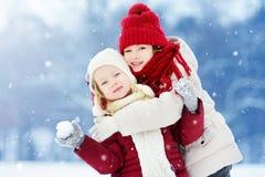 2 прелестных маленькой девочки имея потеху совместно в красивом парке зимы Красивые сестры играя в снеге Стоковое фото RF