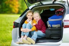 2 прелестных маленькой девочки сидя в автомобиле перед идти на каникулах с их родителями 2 дет смотря вперед для поездки Стоковые Изображения RF