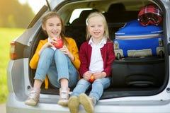 2 прелестных маленькой девочки сидя в автомобиле перед идти на каникулах с их родителями 2 дет смотря вперед для поездки Стоковая Фотография